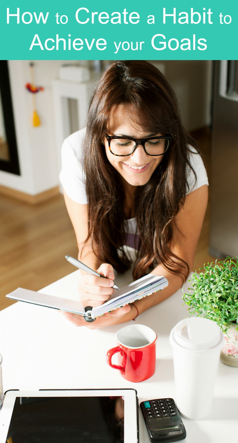 A brunette woman learning how to a create a habit to achieve her goals at her desk writing in her planner with coffee and an ipad on her desk in front of her.