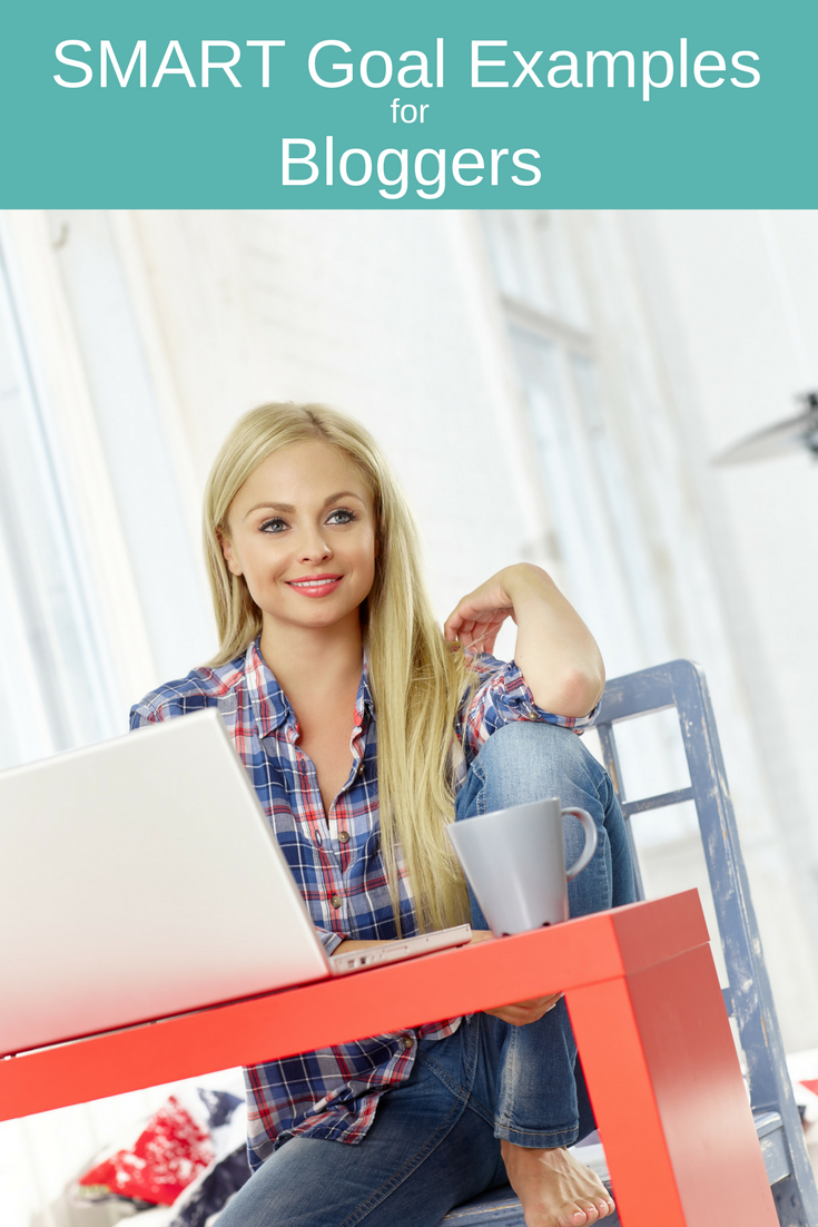 Young blonde woman sitting at her desk with a coffee cup and laptop open in front of her to create her SMART goals examples .