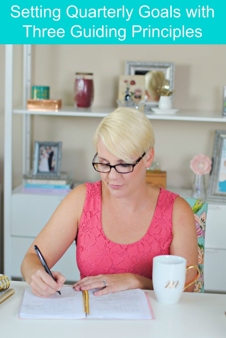 Woman sitting at a desk writing quarterly goals