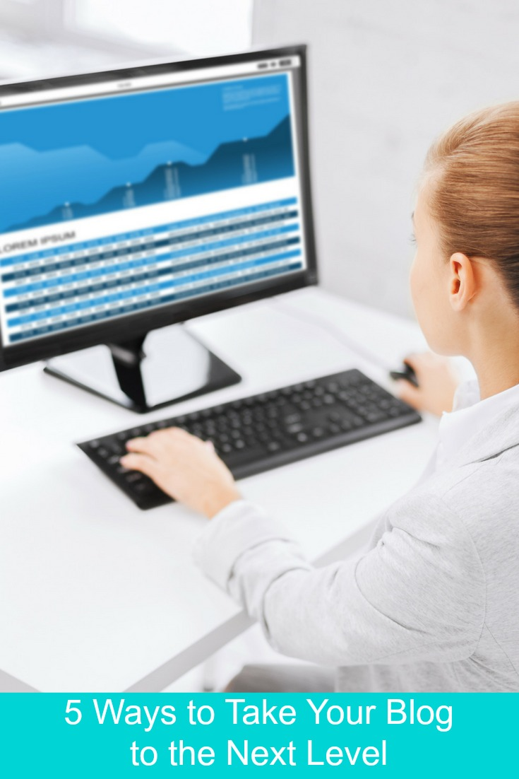 5 Ways to Take Your Blog to the Next Level with a girl look at her computer screen with a graph showing data going up